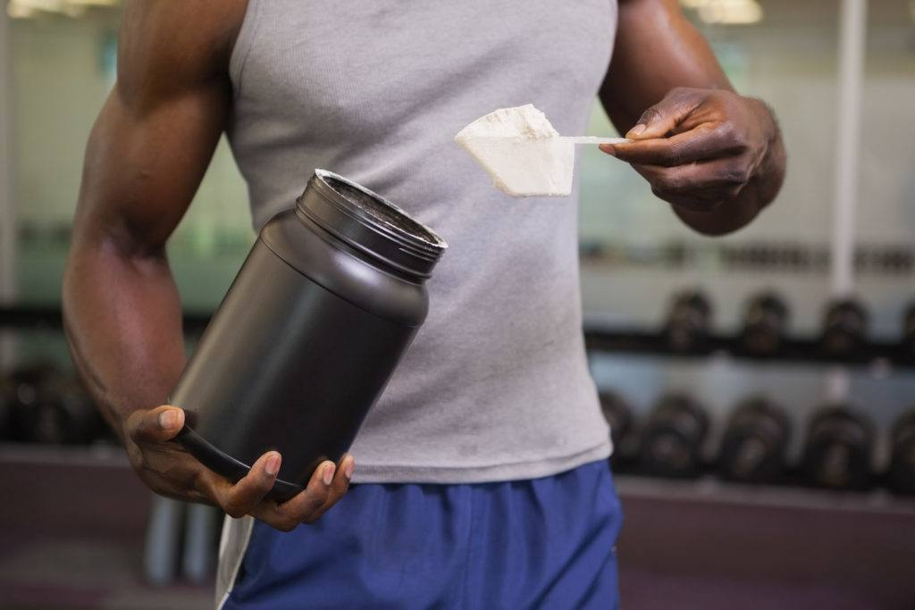 male adding protein powder to his waterbottle