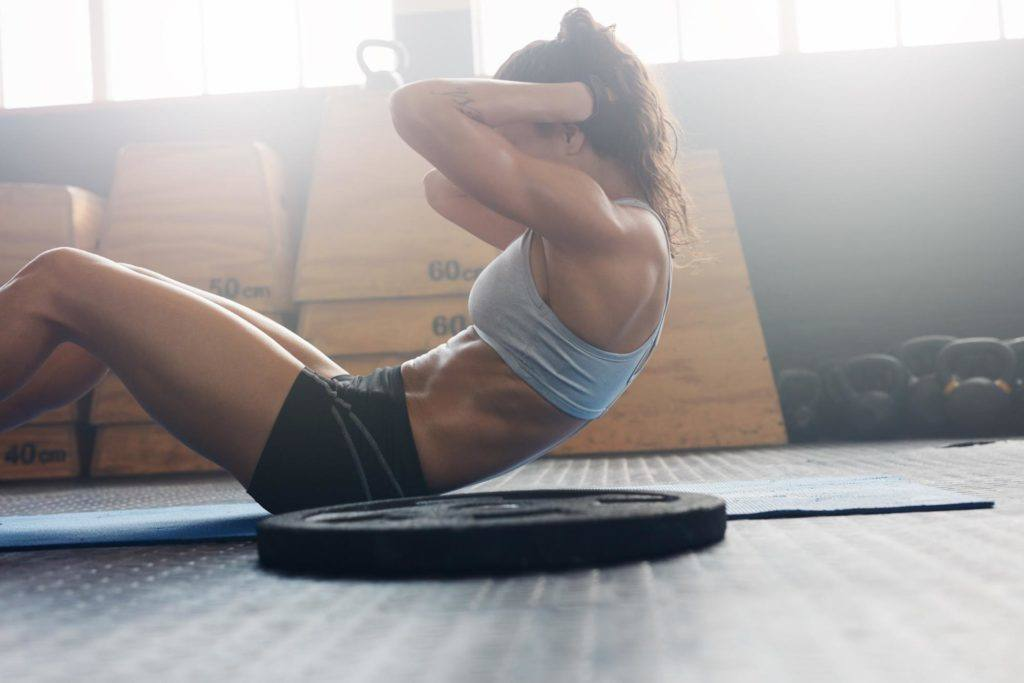 female in ponytail doing sit ups